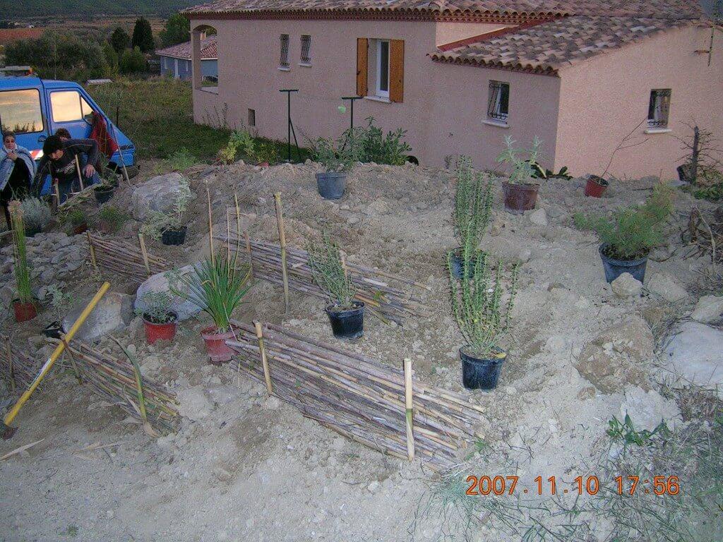 Plantation d'un talus (fin). Le choix des végétaux est fonction du terrain, sec et caillouteux. lezs plantes sont méditerranéennes.